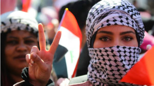 """Picture of a Iraqi woman doing a """"victory"""" hand sign during a march"""
